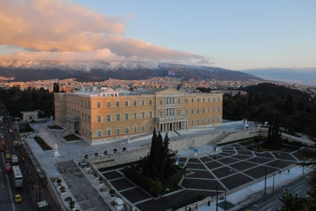 """Hellenic Parliament from high above"" von Gerard McGovern - originally posted to Flickr as Love the clouds over the mountains. Lizenziert unter CC BY 2.0 über Wikimedia Commons - https://commons.wikimedia.org/wiki/File:Hellenic_Parliament_from_high_above.jpg#/media/File:Hellenic_Parliament_from_high_above.jpg"